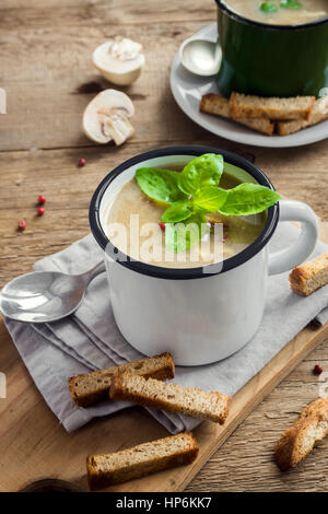 Mushroom soup with croutons and basil in metal mug on rustic wooden background - healthy organic homemade vegetarian - Stock Photo