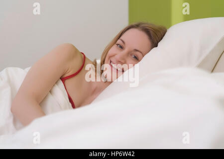 a young woman smiles in her sleeping bag and tent while. Black Bedroom Furniture Sets. Home Design Ideas