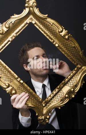 Nobler, zigarrenrauchender Mann, in Anzug und Krawatte im goldenen Bilderrahmen - smoking business man in golden - Stock Photo