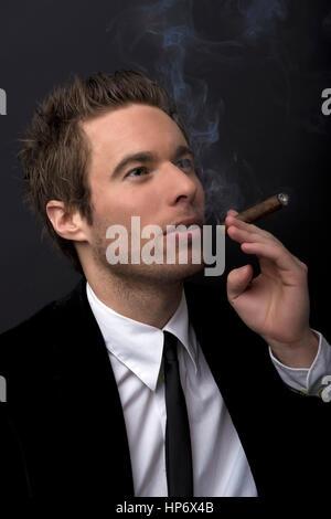 Junger Mann in Anzug und Krawatte raucht Zigarre - man smoking cigar - Stock Photo