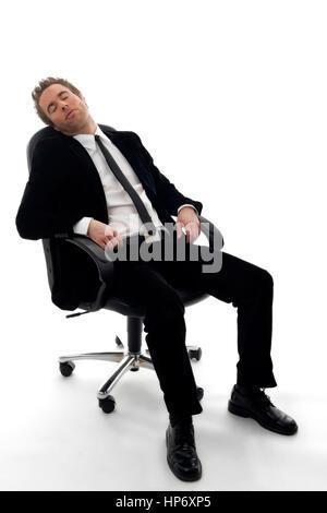 Junger Geschaeftsmann sitzt am Buerostuhl und schlaeft - businessman sleeping