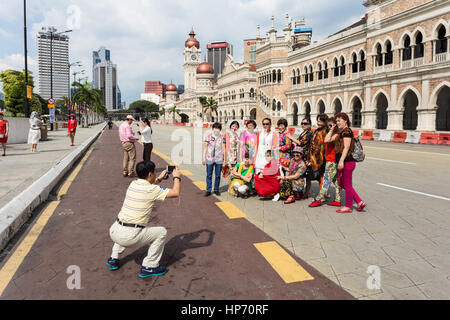 KUALA LUMPUR, MALAYSIA - JANUARY 14, 2017: A group of Chinese tourists poses for a photo in front of the Sultan - Stock Photo