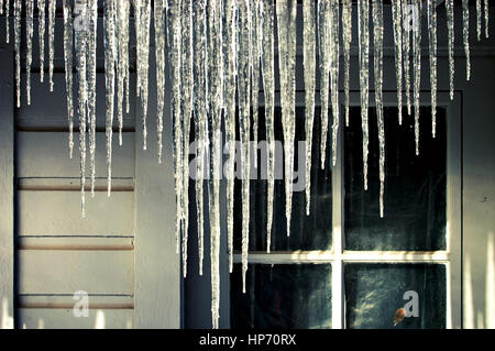 Icicles hanging from a house gutter in the winter. - Stock Photo
