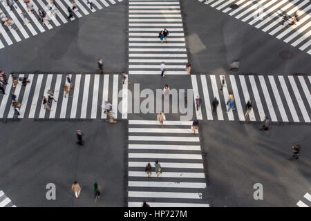 Unidentified people crossing the busy street in Ginza, Tokyo.It is a popular upscale shopping area of Tokyo. - Stock Photo