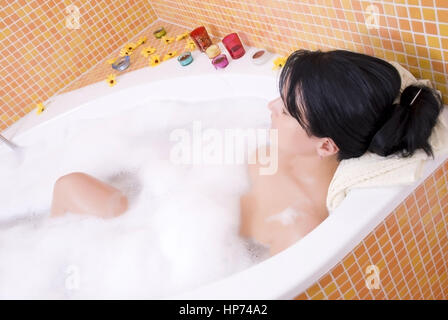 Model released, Junge Frau, 25+, liegt entspannt in der Badewanne - young woman takes a bath - Stock Photo
