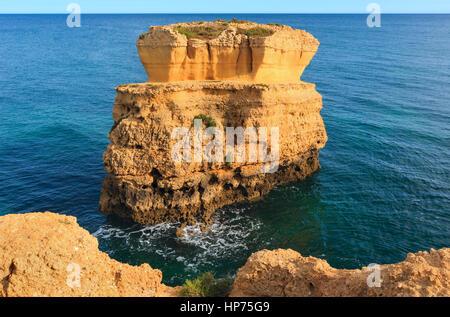 Limestone cliff near shore. Summer evening Atlantic coast view (Praia de Sao Rafael, Albufeira, Algarve, Portugal). - Stock Photo