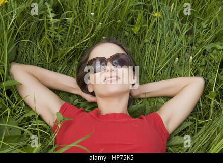 Model released, Junge Frau, 30, liegt entspannt in der Fruehlingswiese - woman relaxing in spring meadow - Stock Photo