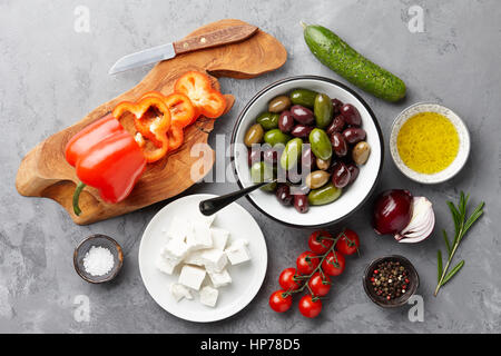 Greek salad basic ingredients: fresh olives, feta cheese, tomatoes, pepper, cucumbers and olive oil on stone background - Stock Photo