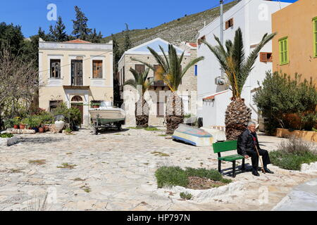 Kastellorizo, Greece-April 4, 2015: Man seats on a bench-small square with boats amidst houses-takes a rest in his - Stock Photo