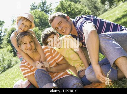Familie mit zwei Kindern, sitzen auf Wiese (model-released) - Stock Photo