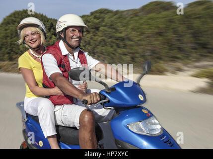 Aelteres Paar faehrt im Urlaub mit Motorroller (model-released) - Stock Photo
