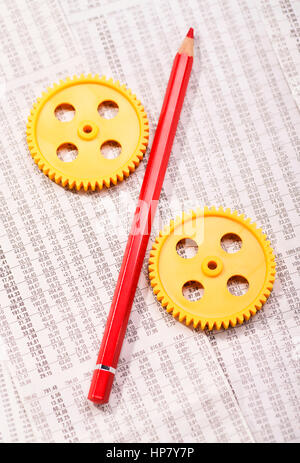 Two gears with a red pencil on tables with share prices - Stock Photo
