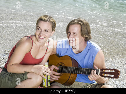 Junges Paar sitzt an Fluss, er mit Gitarre (model-released) - Stock Photo