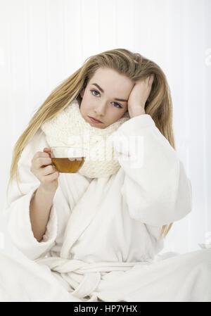 Kranke junge Frau mit Teetasse (model-released)