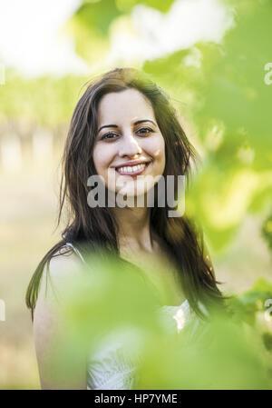 Dunkelhaarige Frau, Portraet im Gruenen (model-released) - Stock Photo