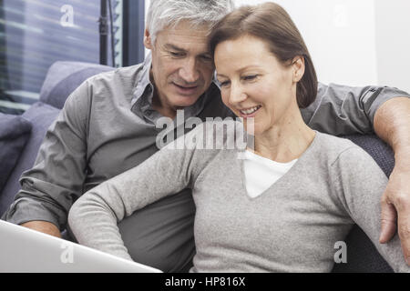 Paar sitzt auf Couch mit Laptop (model-released) - Stock Photo