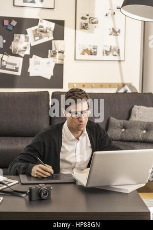 Mann zuhause, arbeitet am Laptop (model-released) - Stock Photo
