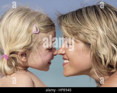 Mutter mit kleiner Tochter am Strand, Nase an Nase, Portraet (model-released) - Stock Photo