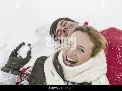 Paar im Winter, liegen lachend im Schnee (model-released) - Stock Photo