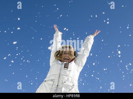 Seniorin wirft lachend Schnee in die Luft (model-released) - Stock Photo