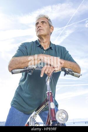 Senior auf Fahrrad, gegen Himmel (model-released) - Stock Photo