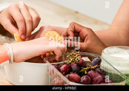 Children eating crisps, snacks at a party - Stock Photo