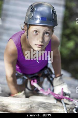 Maedchen an Kletterwand schaut konzentriert nach oben (model-released) - Stock Photo