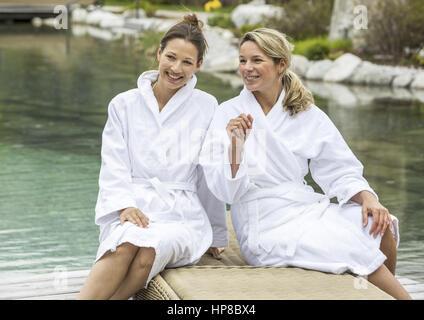 Zwei Frauen im Bademantel sitzen auf Liege (model-released) - Stock Photo