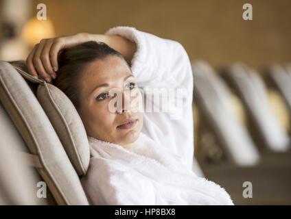 Dunkelhaarige Frau im Bademantel in Ruheraum (model-released) - Stock Photo
