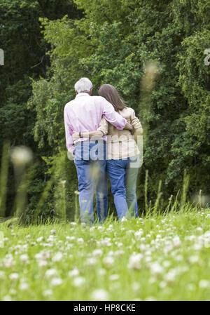 Seniorenpaar beim Spazierengehen an Waldrand, von hinten (model-released) - Stock Photo