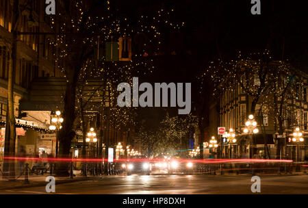 Vancouver, Canada - January 28, 2017: Gastown, Vancouver at night with lights in the trees and light trails from - Stock Photo