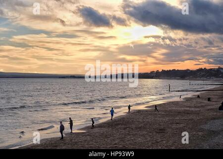 Bournemouth, Dorset, UK. 20 February 2017. Youngsters skim stones on the beach as the sun sets on a day where locally - Stock Photo