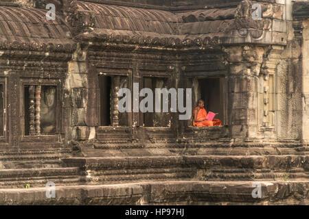 buddhistischer Mönch sitzt in einem Fenster, Tempelanlage Angkor Wat, Kambodscha, Asien  |  buddhist monk sitting - Stock Photo