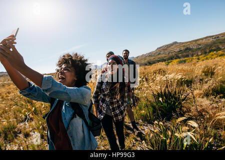Happy young woman taking pictures of friends while hiking. Group of friends on country walk taking selfie. - Stock Photo