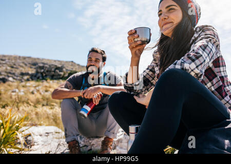 Young woman drinking coffee and resting with friend during hike. Two young friends taking a break during hike. - Stock Photo