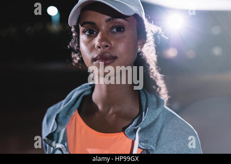 Close up shot of fitness woman in city at night. Beautiful female runner looking away. - Stock Photo