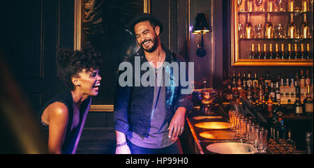 Happy couple at lounge disco bar counter and laughing. Young people having fun in a club. - Stock Photo