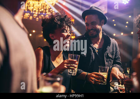 Group of young friends on a night out at pub. Happy young men and women having drinks and smiling at night club. - Stock Photo