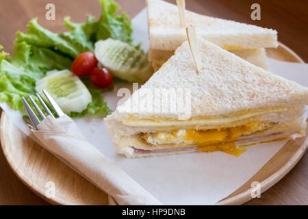 slice ham cheese egg sandwich breakfast with fresh vegetable cucumber on wooden table ,selective focus - Stock Photo
