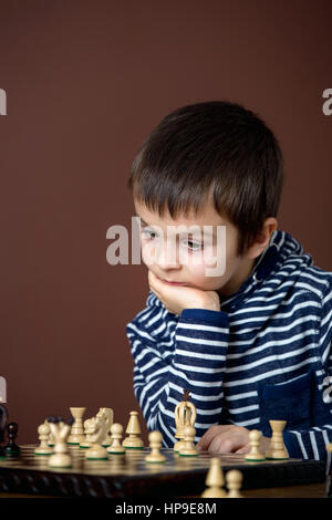 Little boy, playing chess. Smart kid, isolated, playing chess. Children playing intelligent game - Stock Photo