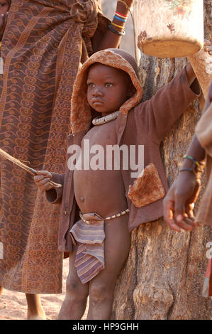 KAOKOVELD, NAMIBIA - OKT 13, 2016: Unidentified Himba boy in a small village. The child is helping protecting the - Stock Photo