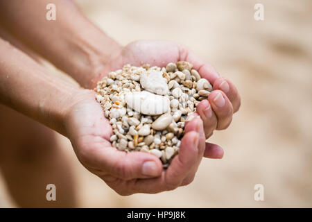 woman hands holding pebble of mixed white biege and terracotta color shot on Kaputash beach of Turkey with focus - Stock Photo