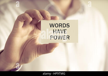 Closeup on businessman holding a card with text WORDS HAVE POWER, business concept image with soft focus background - Stock Photo