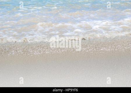 Soft sea water edge close up rippling onto beach - Stock Photo