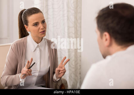Working with client. Attractive young female therapist looking at her client and showing V sign while helping him - Stock Photo
