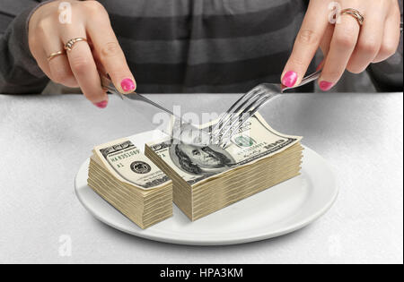 Hands cut money on plate, reduce funds concept - Stock Photo