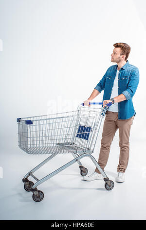 handsome young man standing with shopping trolley and looking away - Stock Photo