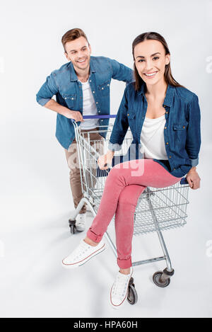 woman sitting on shopping cart with man looking at her - Stock Photo