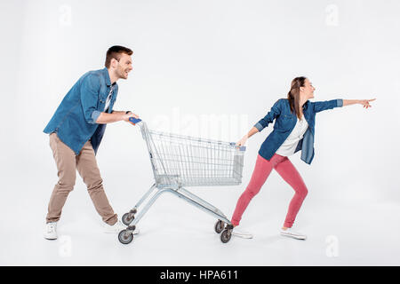 woman pointing way and while pulling shopping cart with man - Stock Photo