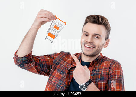 smiling man pointing at shopping cart model and looking to camera - Stock Photo